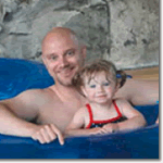 Father and young daughter in float in a swimming pool.